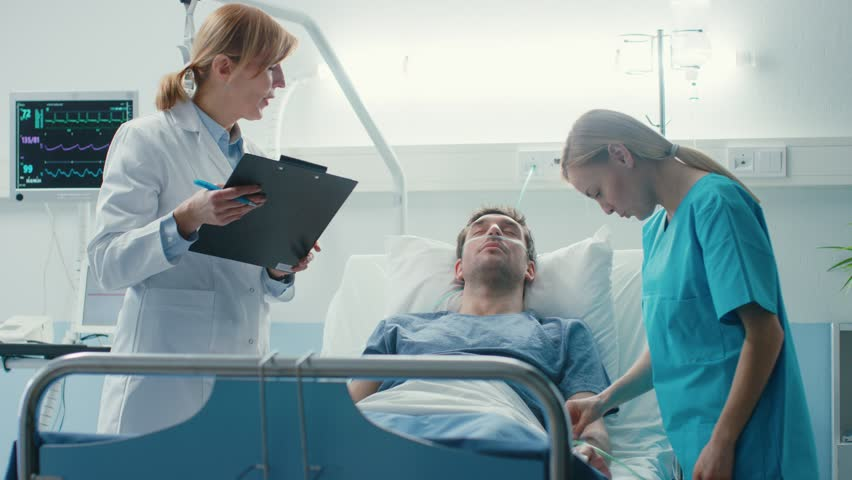 In the Hospital Sick Male Patient Lies on the Bed, Professional Female Doctor Writes in the Patient Chart, Addresses Nurse who Checks Drop Counter and Increases Dose of the Pain Killer. | Shutterstock HD Video #1009295519