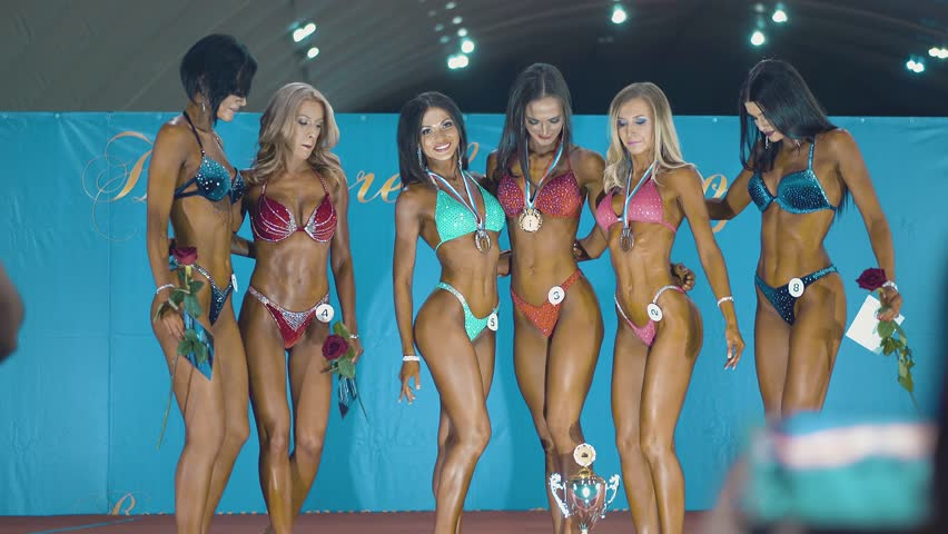 Beautiful girls who are engaged in fitness, during the beauty contest. They stand on stage in bikinis and shoes, posing in front of the camera.