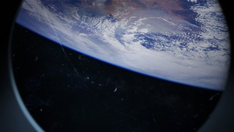 Earth is seen through scratched window of a spaceship