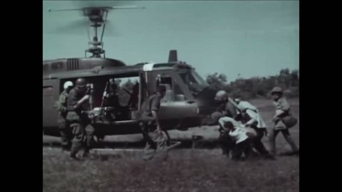 CIRCA 1960s - The crew of a Huey combat helicopter belonging to the US Military evacuate Vietnamese villagers.