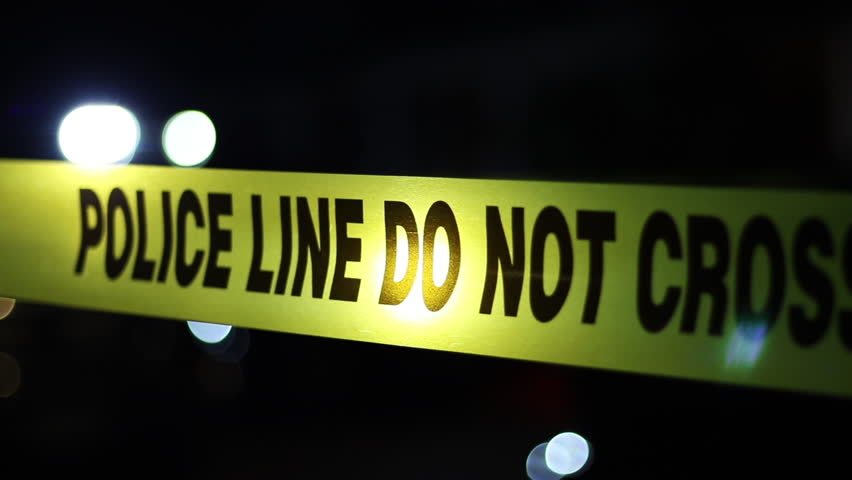 Police tape at a crime scene at night with flashing cop lights blurred in the background.