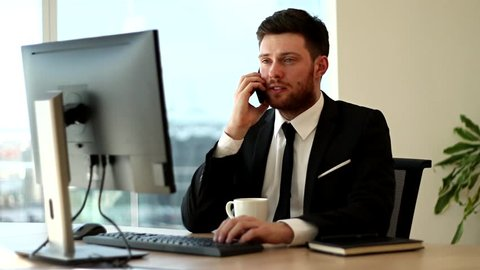 Businessman talking on the phone. Typing while talking on the phone