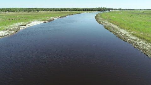 High speed low pass of a river/stream through a grassland area.