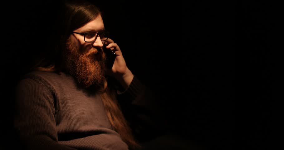 Bearded man talking on the phone in the darknes
