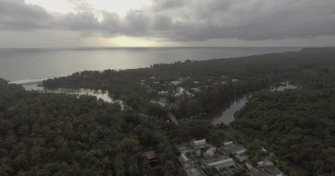 An aerial view of green foliage, sea and a sunset among the clouds.