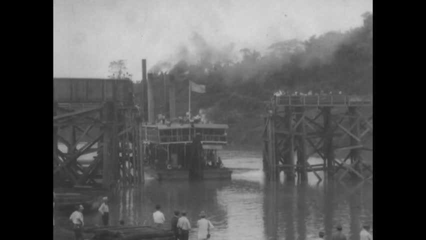 CIRCA 1914 - A ferry moves through a lock gate and a tugboat travels on the Chagres River during the construction of the Panama Canal. | Shutterstock HD Video #1009420859