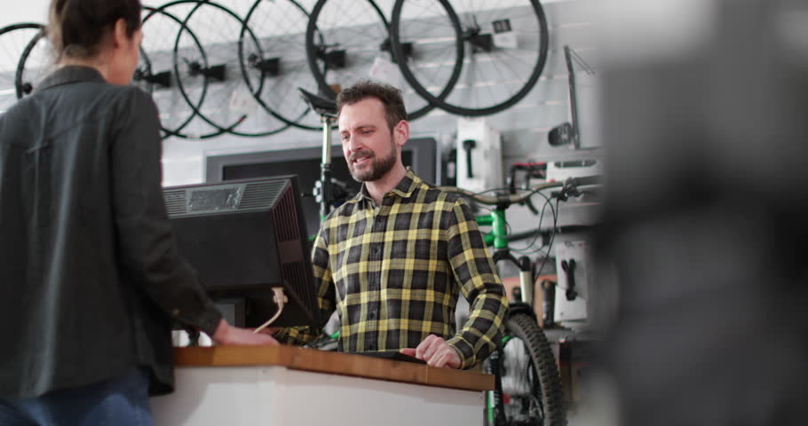 Small business owner serving customer in a bicycle store