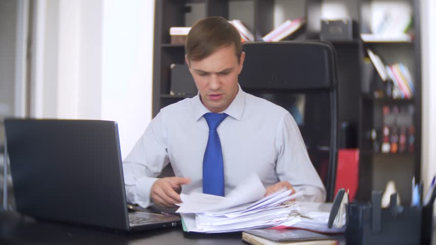A businessman who scans documents, frowns, using a laptop, does not perform an urgent task in the office, there is not enough time, 4k