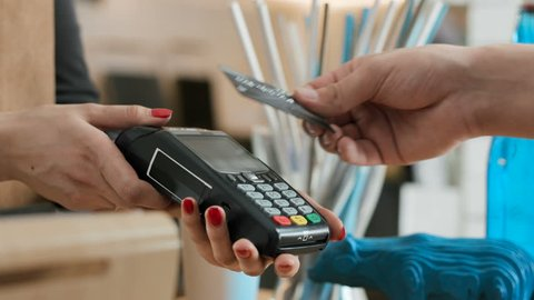 Female employee near cash desk of restaurant store for breakfast or lunch. Plastic debit of male buyer with cashless wallet of e-money for pos reader and checkout. Morning life of people slowmotion