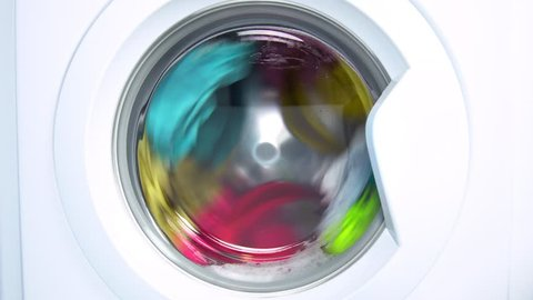 Washing machine washes colored clothing and sheets. Cylinder spinning. Nobody