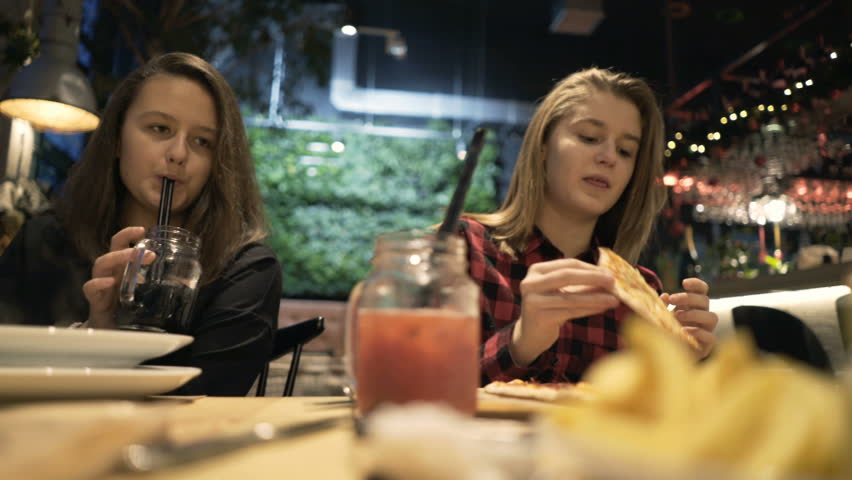 Two teenage girlfriends eating meal and drinking beverage sitting in cafe