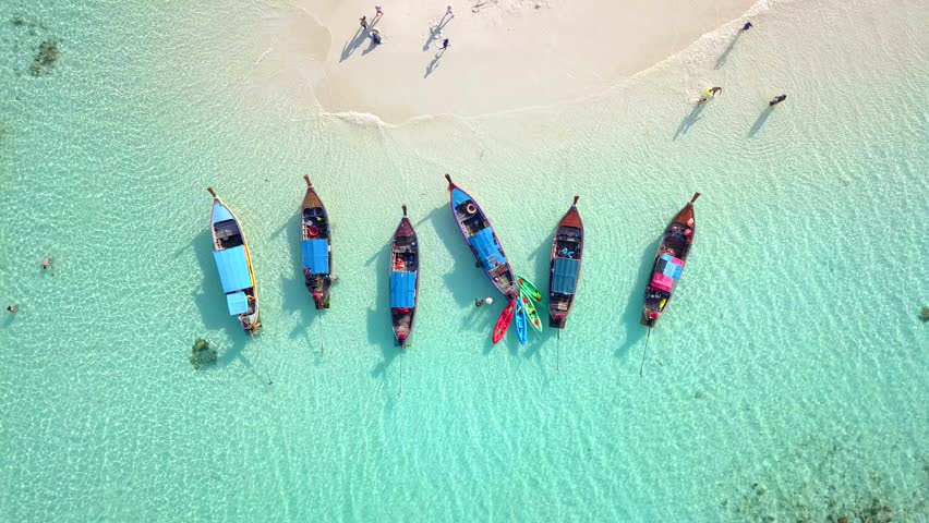 Aerial view of Long Tail Boats floating on crystal water along the sand beach in Thailand.Summer Aerial View footage in 4K.