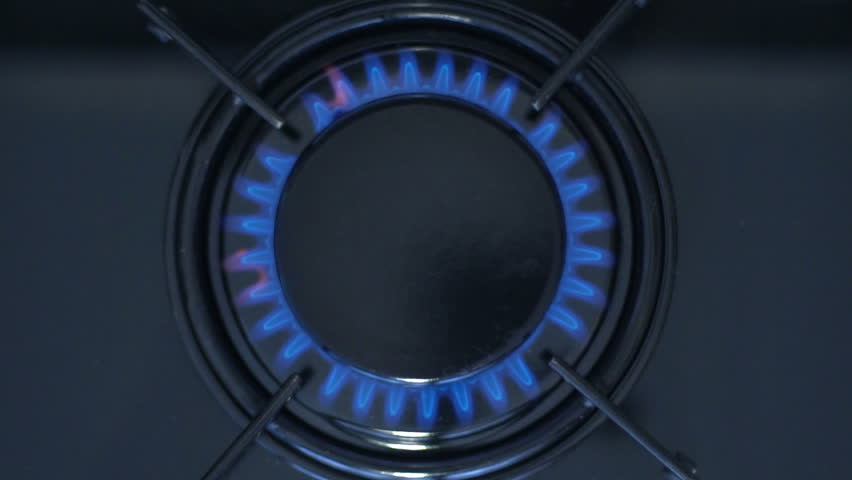 Kitchen burner turning on.Stove top burner igniting into a blue cooking flame.  Natural gas inflammation, close up, slow motion.  | Shutterstock HD Video #1009467299