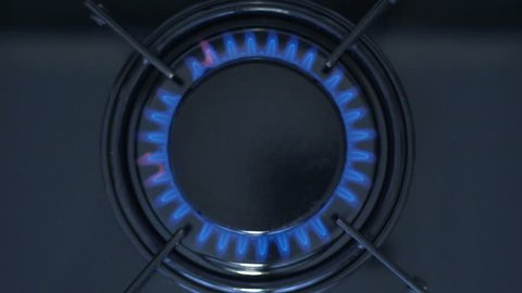 Kitchen burner turning on.Stove top burner igniting into a blue cooking flame.  Natural gas inflammation, close up, slow motion.
