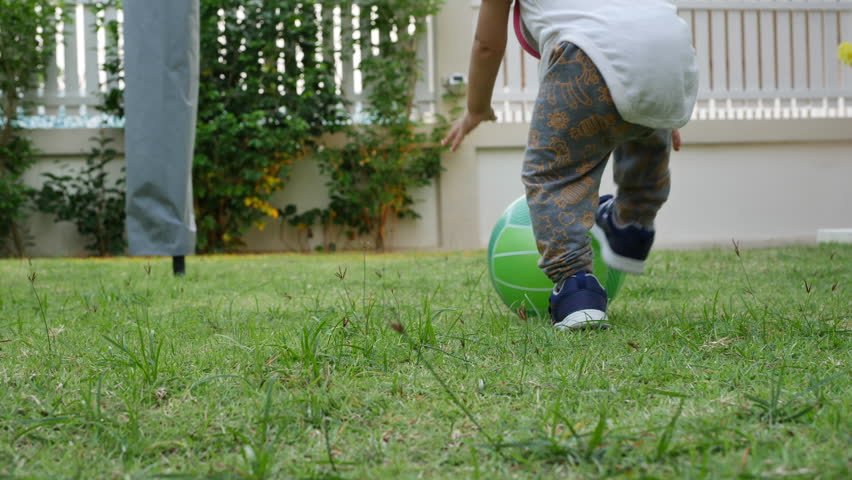 Slow-motion, cute child toddle falling on green grass playing ball | Shutterstock HD Video #1009469399