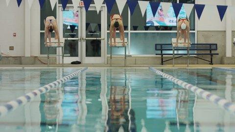 Surface level view of girls racing in swimming pool lane / Provo, Utah, United States