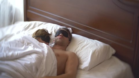 a married couple woman and a man in a mask for sleeping, sleep in bed on a pillow in the daytime. 4k.