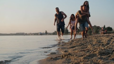 Tilt up of happy young man carrying his laughing girlfriend and running along beach with cheerful group of friends on hot summer evening