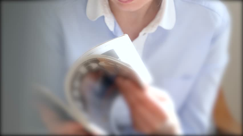 Detail of young woman reading magazine business newspaper