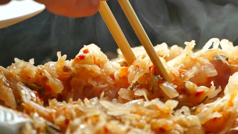 Stewed cabbage is prepared in a frying pan. Take stewed cabbage on a plate. Chinese chopsticks..