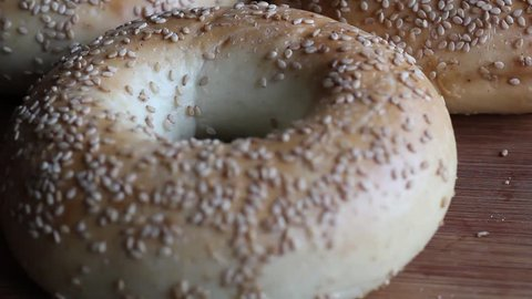 Tilt up and down of fresh bagels on a wooden surface. HD video.