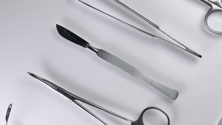 the doctor takes a scalpel from the table with surgical instruments, close-up