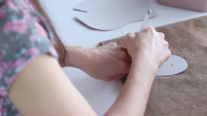 Women's hands create a textile product, toy, pattern