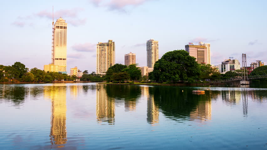 Sri Lanka. View of Beira Lake in Colombo, Sri Lanka with buddhist temple and modern buildings at sunrise. Morning time-lapse. Clear sky, zoom in