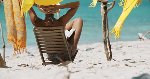 woman with arms behind head sitting in teak chair reading a book on tropical beach
