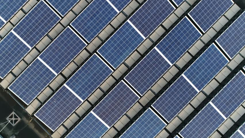 Aerial top down view moving up above solar panels PV modules mounted on flat roof photovoltaic solar panels absorb sunlight as a source of energy to generate electricity creating sustainable energy 4k