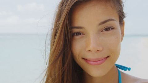 Happy smiling young Asian mixed race brunette woman on beach vacation. Healthy ethnic girl with a natural toothy smile. Portrait of beautiful model looking at camera closeup.