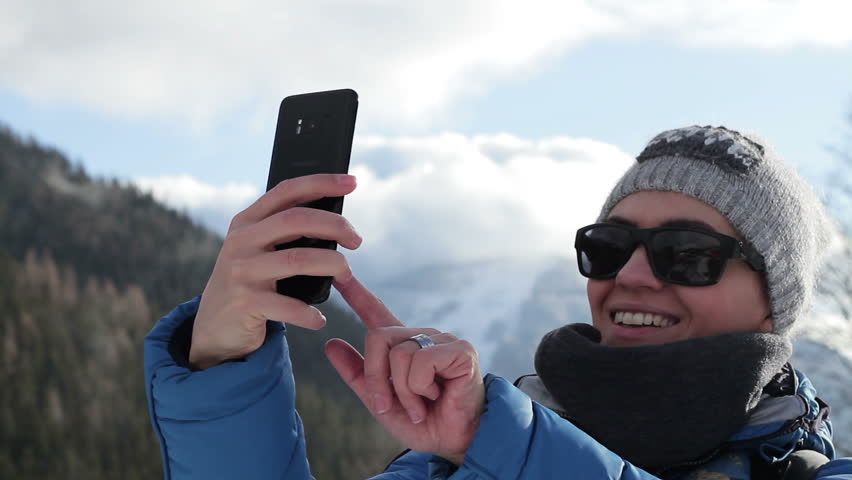Young woman taking a self portrait with her smartphone in the mountains, Alps, Austria  | Shutterstock HD Video #1009596569