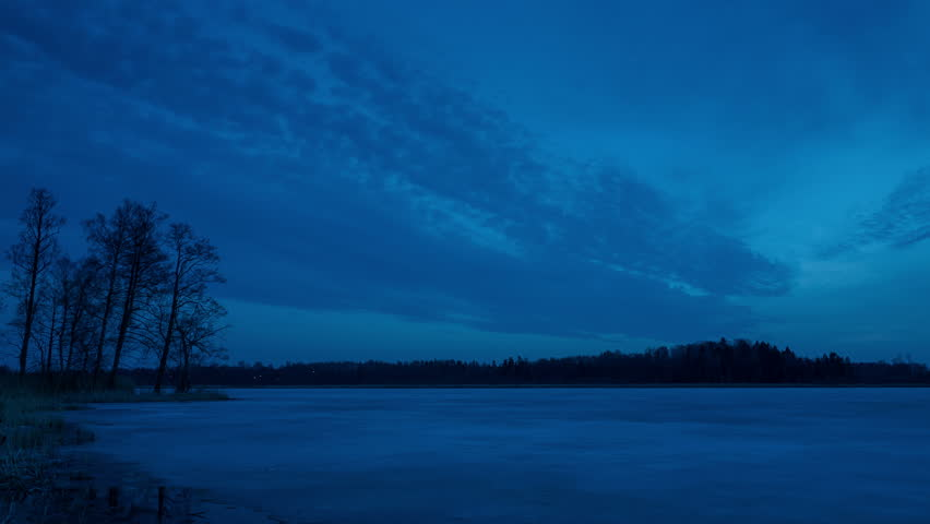 Beautiful 4k timelapse video of nice nature and landscape on spring dusk evening in Sweden Scandinavia Europe. Wonderful fresh blue sky and frozen ice lake at sunset. Forest at horizon. Calm, peaceful