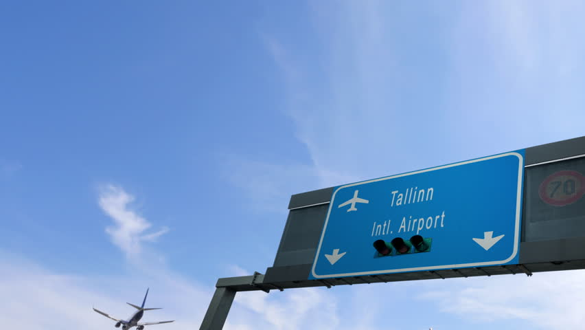 airplane flying over tallin airport signboard