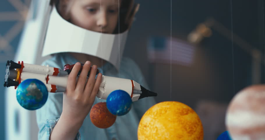 CU Cute little girl wearing cardboard astronaut helmet flying toy rocket with attached red sports roadster car to it. 4K UHD 60 FPS SLOW MO | Shutterstock HD Video #1009648289