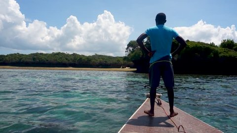 young barefooted African man on a wooden boat moored on the shore of a deserted tropical island