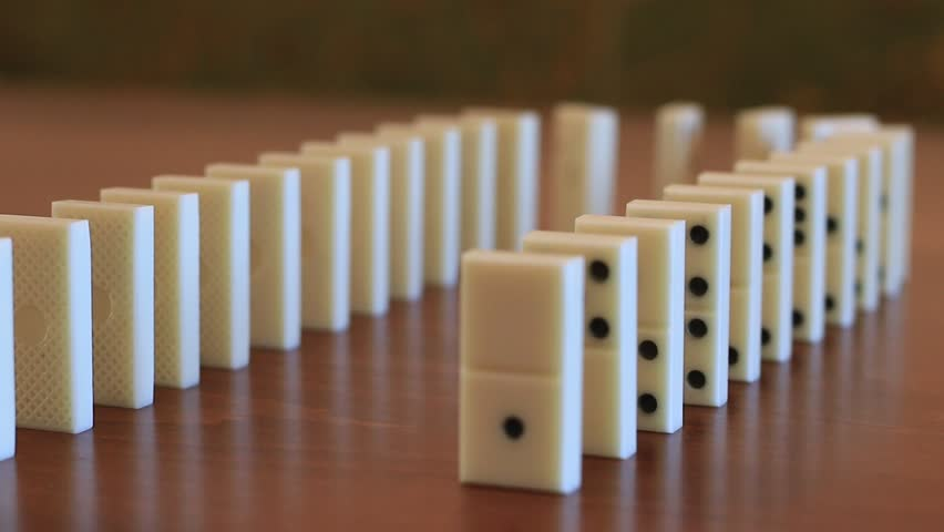 Domino effect - row of white dominoes falling down