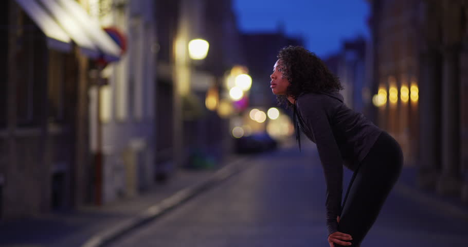 Black woman jogger in the city at night catching her breath. Female athlete taking a break from jog on city street. 4k | Shutterstock HD Video #1009669409
