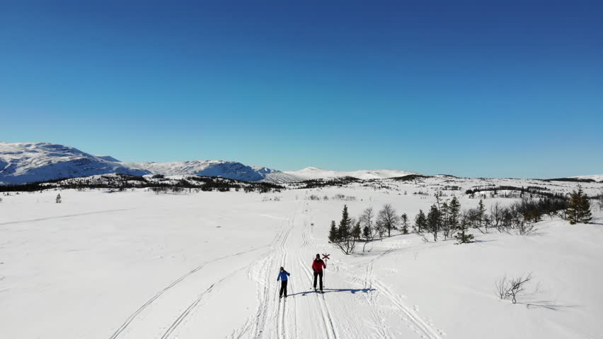 Aerial view of a woman and a kid, cross country skiing on a track in the swedish mountains