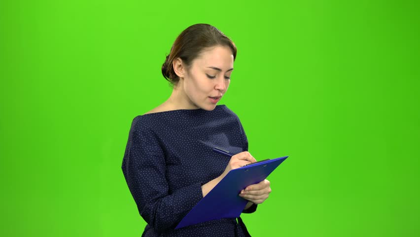 Accountant records the data in a paper tablet. Green screen
