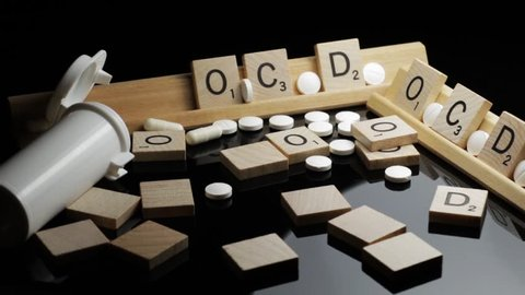 OCD concept spelled in text with pharmaceutical medication on a black table. Obsessive Compulsive Disorder and behavioral health issues.