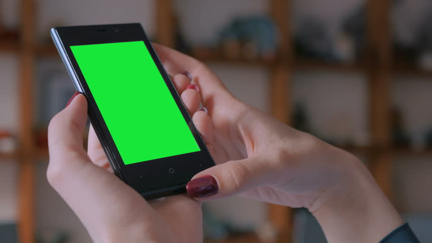 Woman looking at vertical smart phone with green screen in pottery workshop, studio. Close up shot of woman hands with mobile phone #1009726709