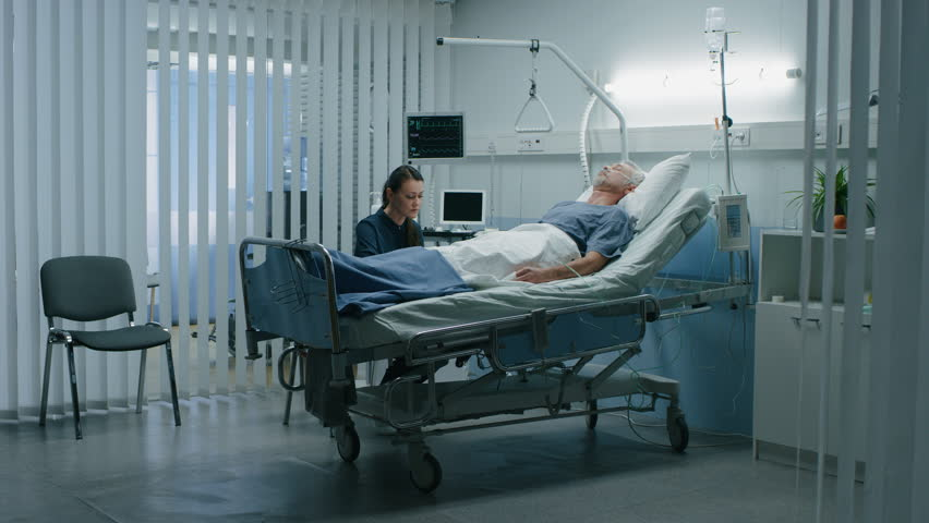 In the Hospital Man Lying in Bed while Daughter Worries and Waits when He'll wake up. Time Passing Time-Lapse Effect. Shot on RED EPIC-W 8K Helium Cinema Camera.