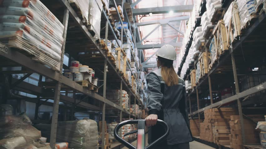 Following shot of female industrial worker in hard hat walking through along shelves with trolley for the warehouse. Female laborer in uniform passing by, pulling trolley stuffed with piled boxes | Shutterstock HD Video #1009730489