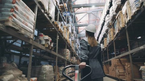 Following shot of female industrial worker in hard hat walking through along shelves with trolley for the warehouse. Female laborer in uniform passing by, pulling trolley stuffed with piled boxes