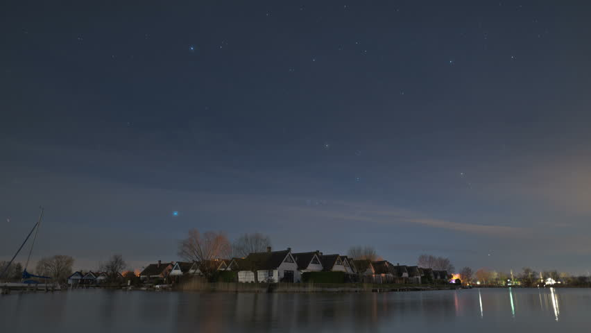 Time-lapse at night of moving stars and clouds above terraced houses in the cottage settlement of Seepark Weiden at Lake Neusiedlersee in Austria. Some airplanes are flying around.