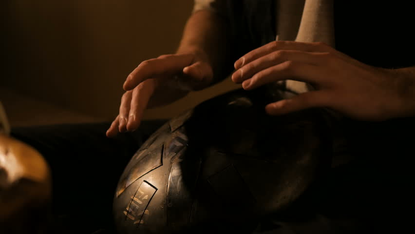 Man playing tank drum or hang at home. Warm romantic illumination, low key. Relaxation, meditative and traditional music concept. Close up shot