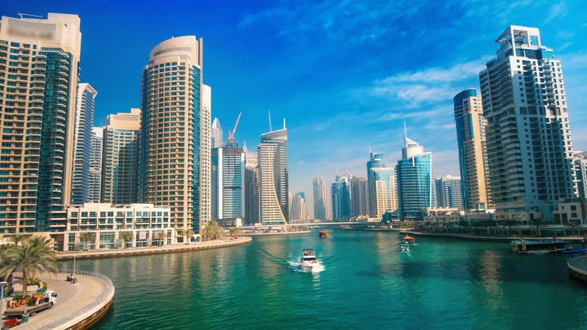 Dubai Marina under blue sky, with boats and skyline, hyperlapse footage