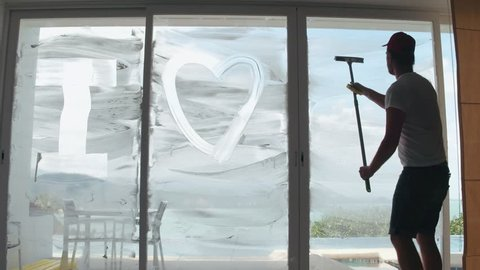 Funny housekeeper writing i love you on soap window glass during cleaning in room. Man cleaning and washing panoramic window in luxury apartment