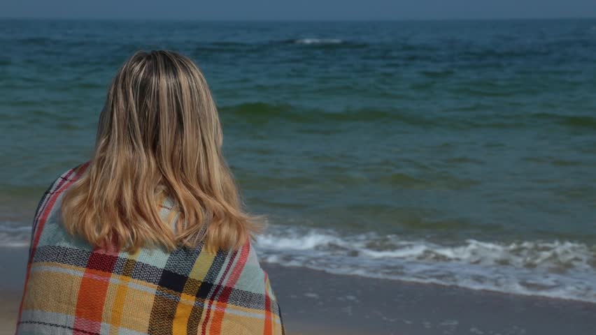 Head and shoulder back view of young blondy woman sitting alone on sandy beach and looking at sea. Back covered with cozy blanket. Spring, autumn or cold summer day. With copyspace. Focus at woman.